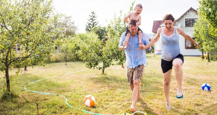 Familie løber i haven og leger med vand